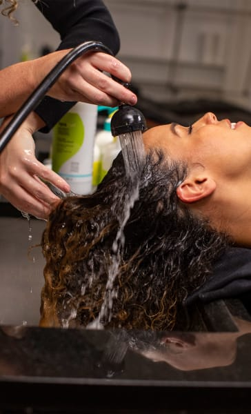 woman at sink getting her curly hair rinsed with water