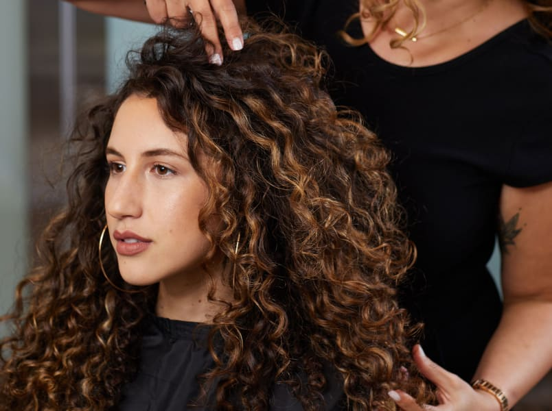 stylist hands in clients curly hair
