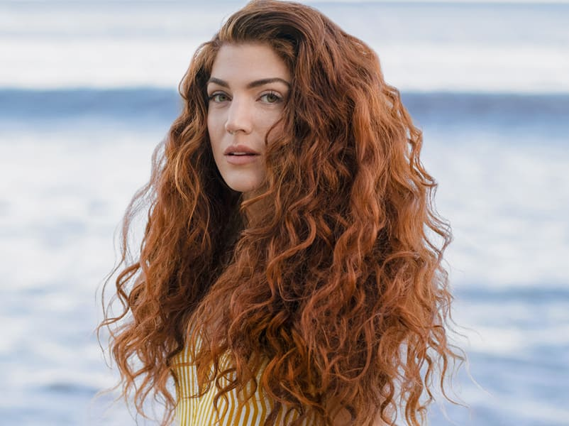woman with red wavy hair on the beach