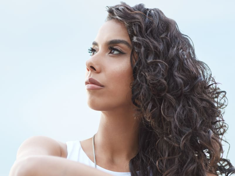 woman with long dark wavy hair looking away