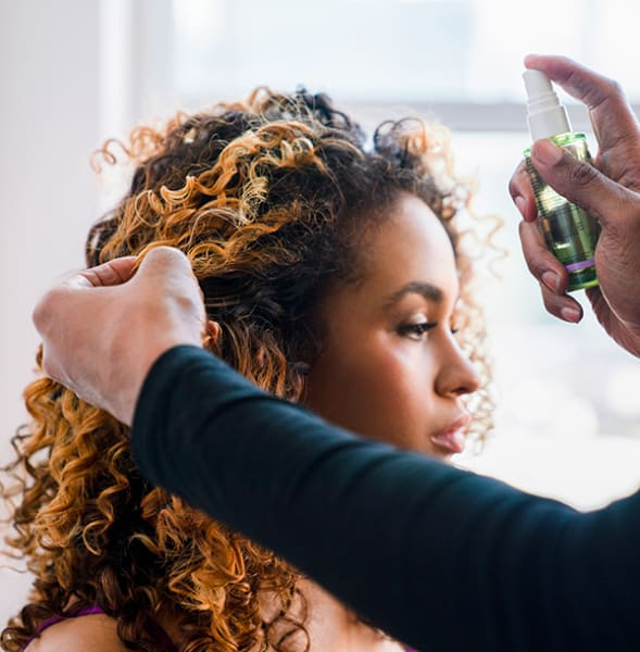 woman with curly hair getting high shine sprayed on hair