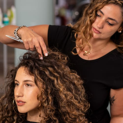 hair stylist smiles at curly hair client