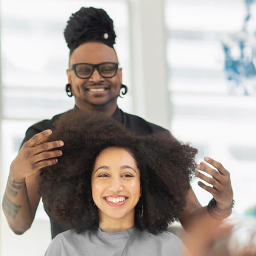 hair stylist fluffs curly hair client