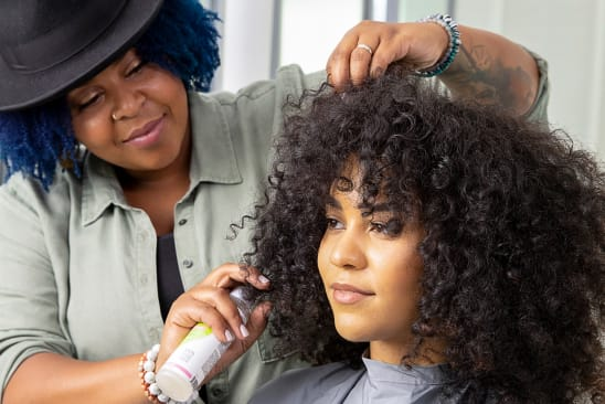 curly hair stylist spraying curly hair customer