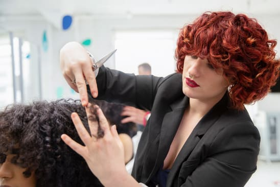 red curly hair stylist cutting curly hair