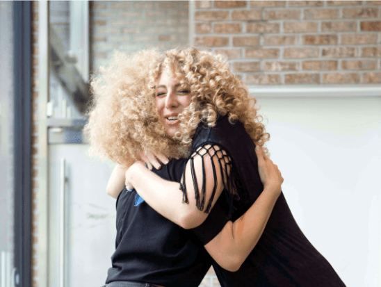 two blond curly hair women hugging