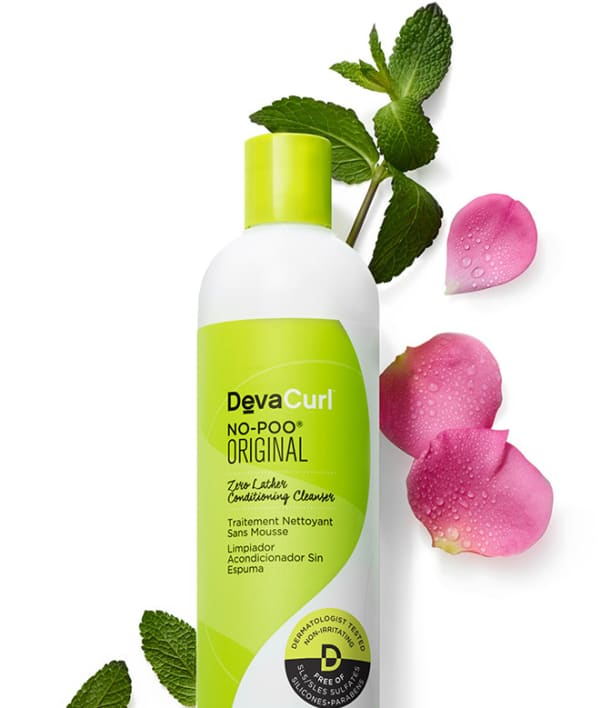 bottle of devacurl no-poo original surrounded by flower petals