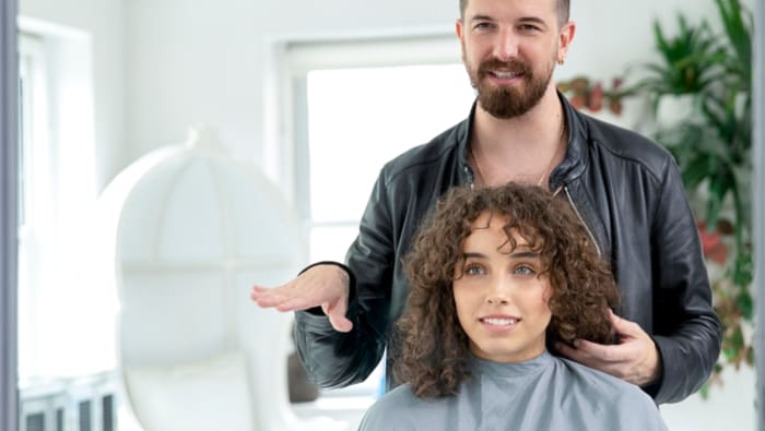 male hair stylist talks to curly hair woman in a chair