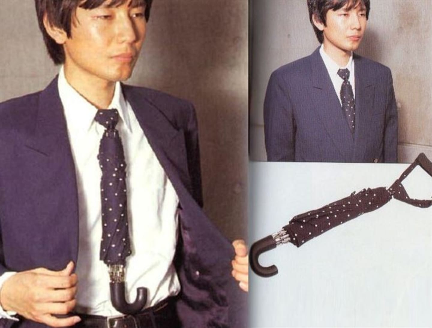 A man in a business suit wears a tie that appears to also be an umbrella. He opens his jacket to reveal an umbrella handle projecting from the end of his tie.