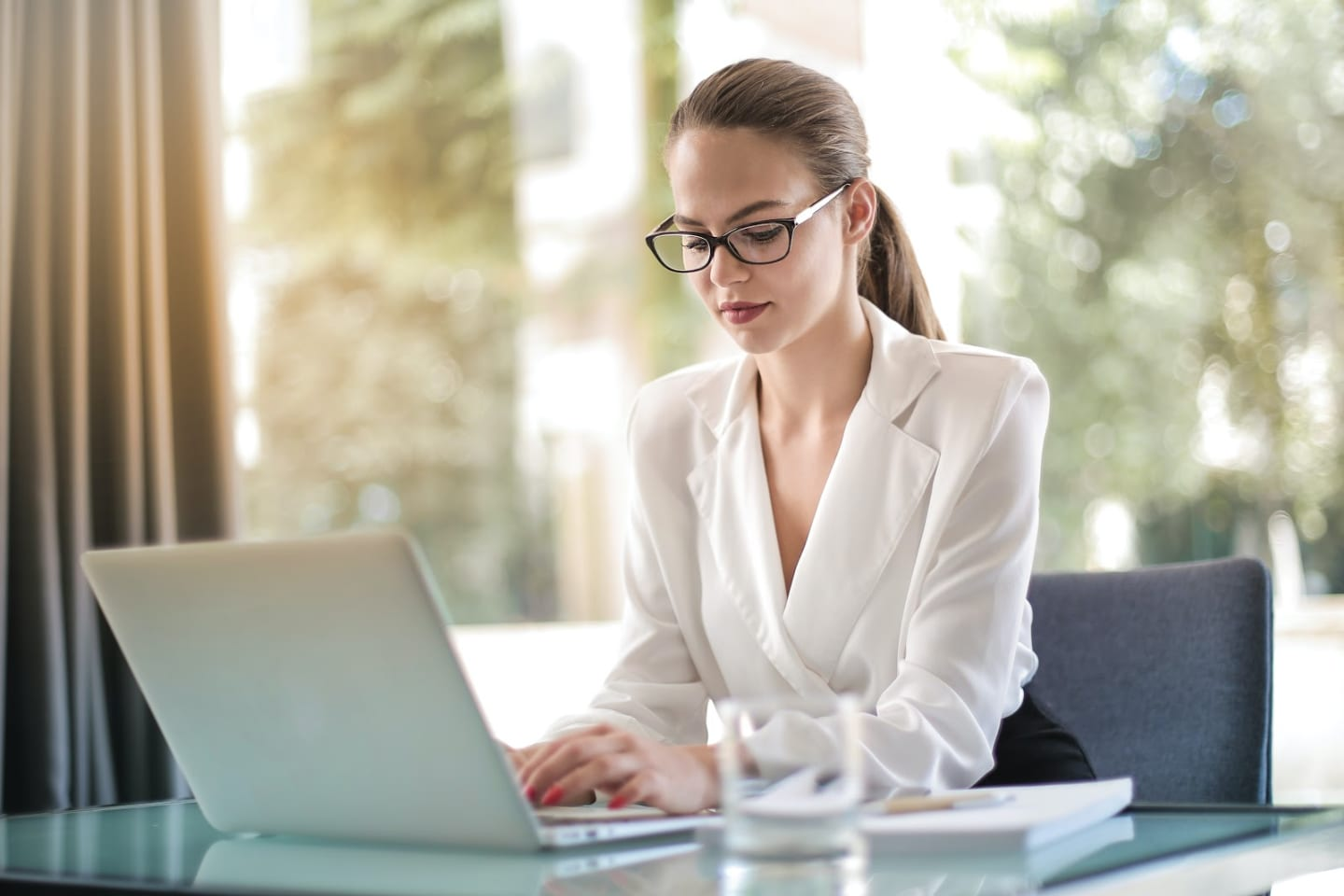 A professionally dressed woman works at her laptop.