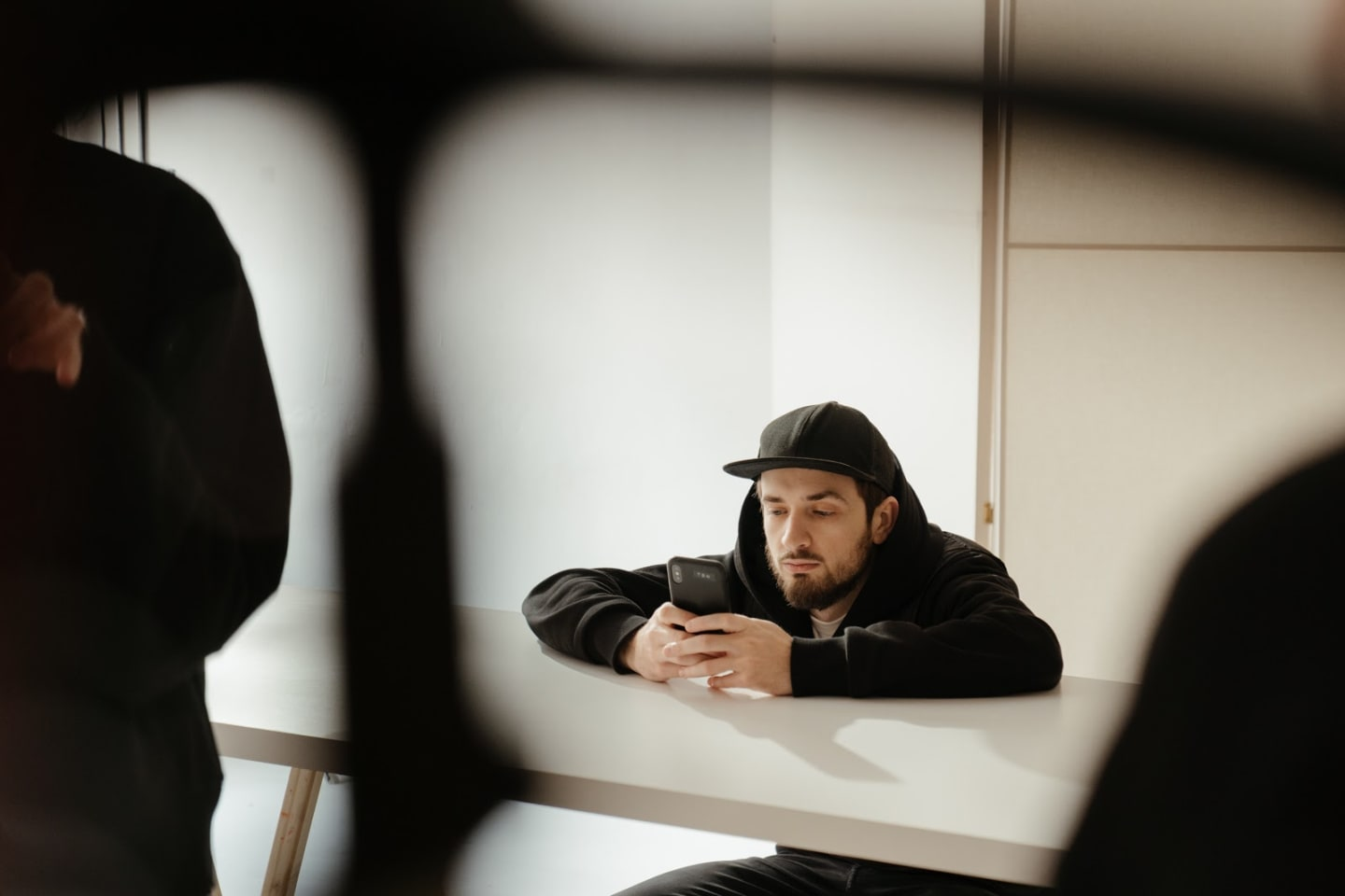 A man in a black hoodie and baseball cap sits at a desk and gazes into the phone he holds in both hands.