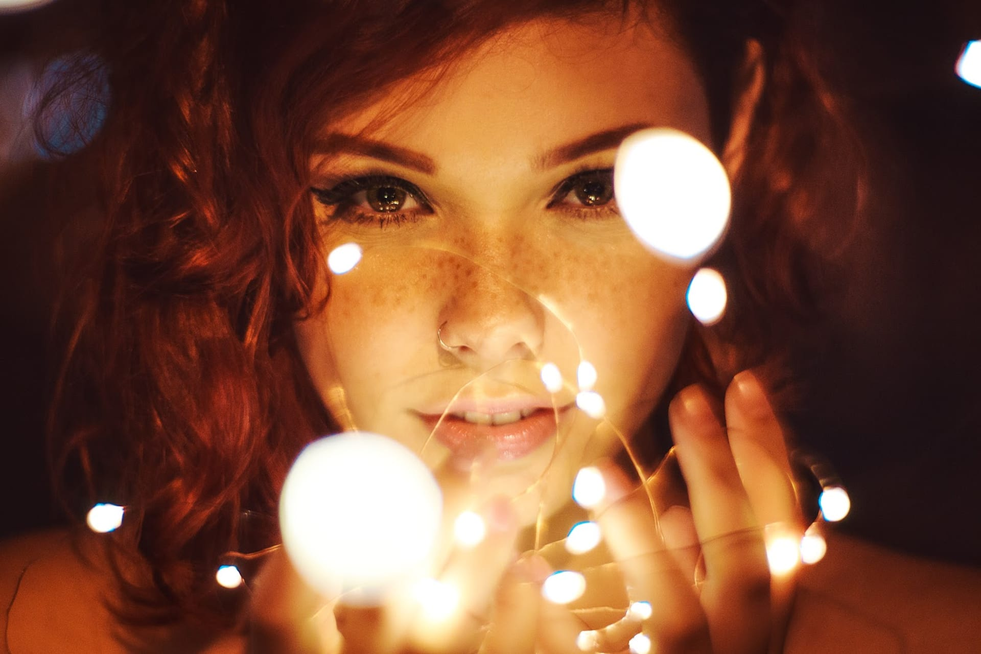 A young woman gazes mysteriously at us through a series of lights held in her fingers