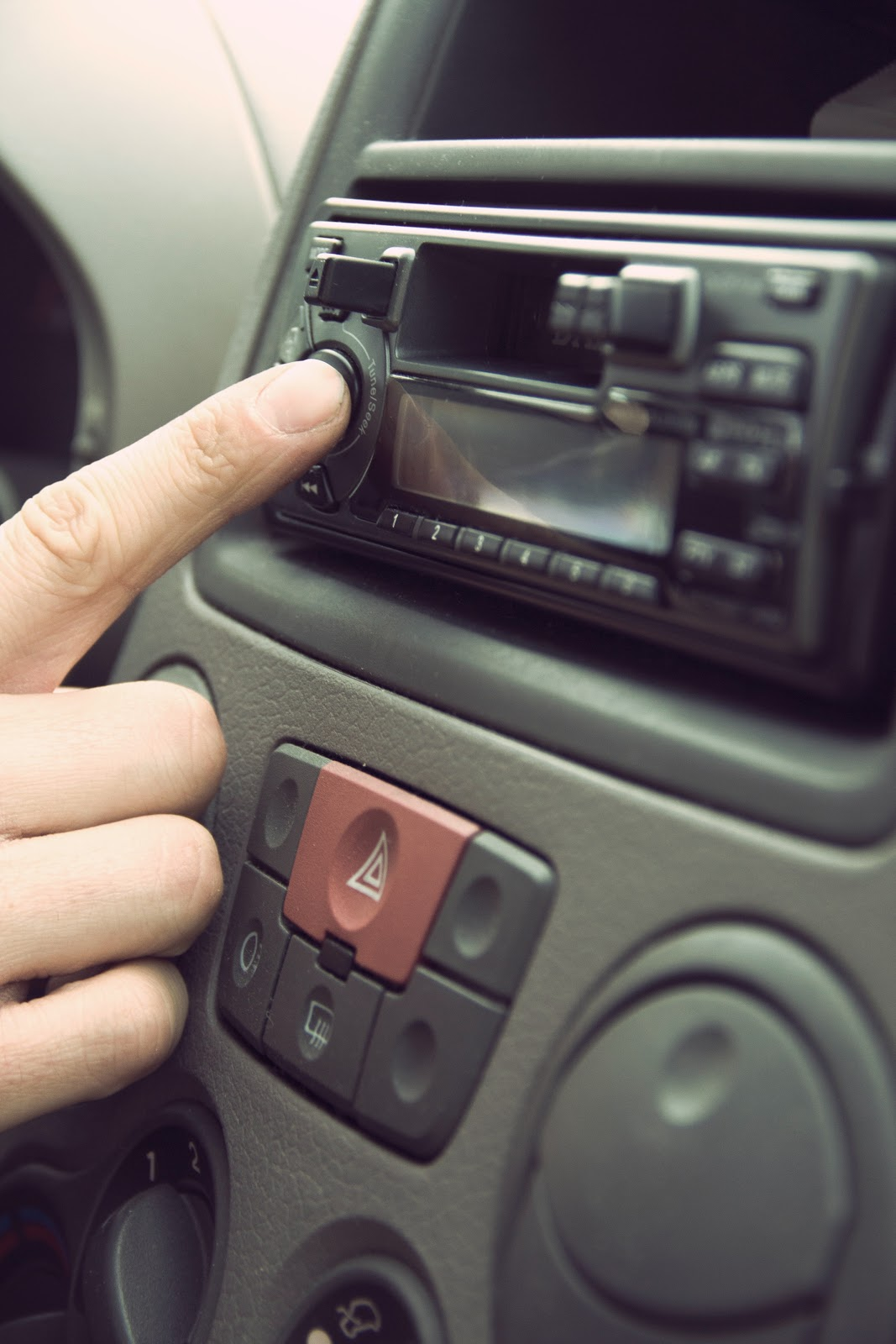 A close up of a driver's hand reaching towards an in-car stereo featuring a cassette player.