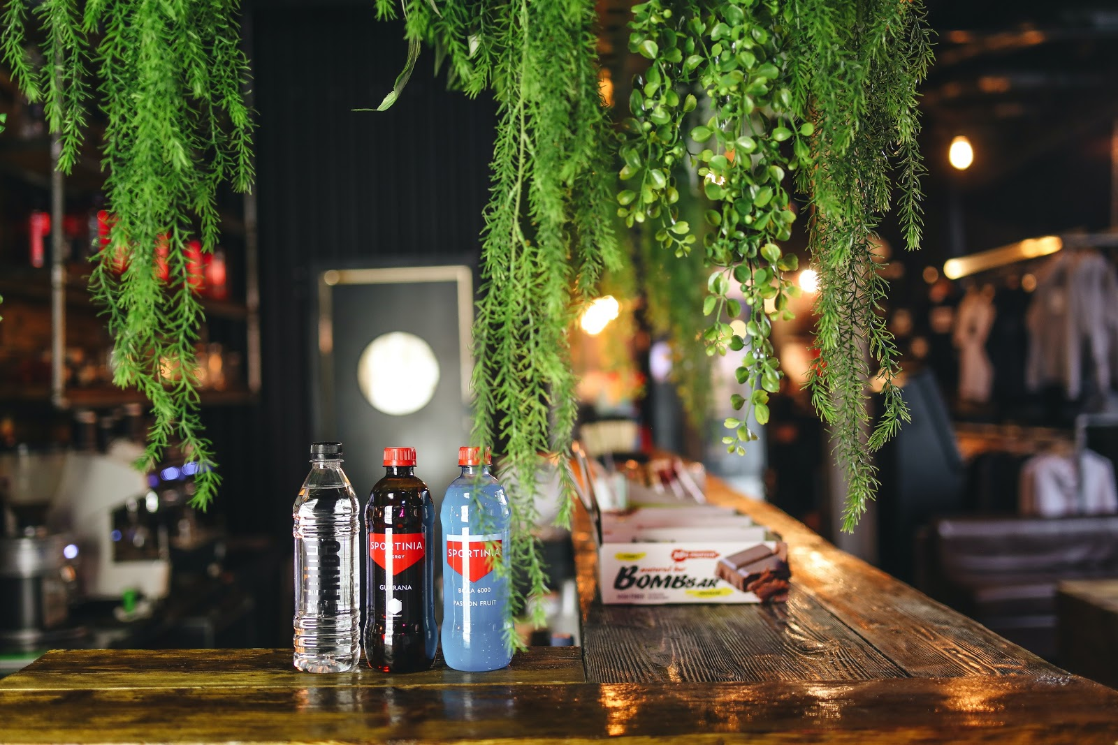 An attractive bar with overhanging green foliage featuring an array of bottled products.