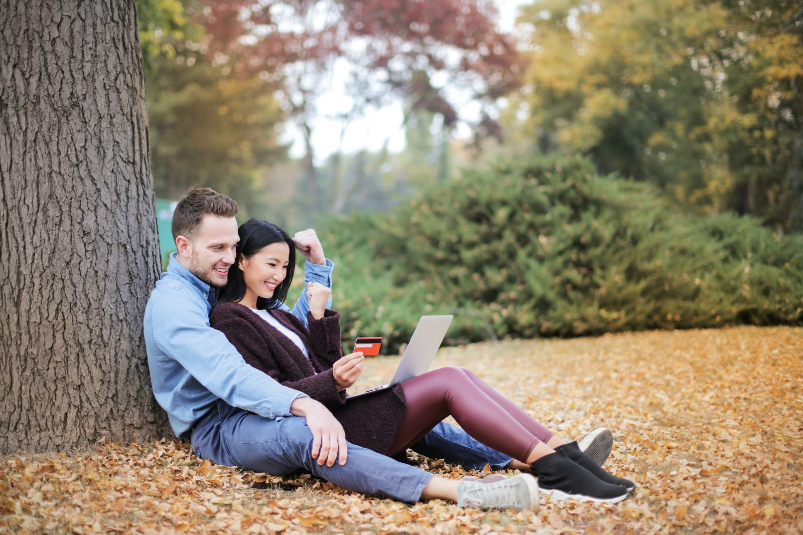 A couple sharing a tablet computer or latop recline against a tree.