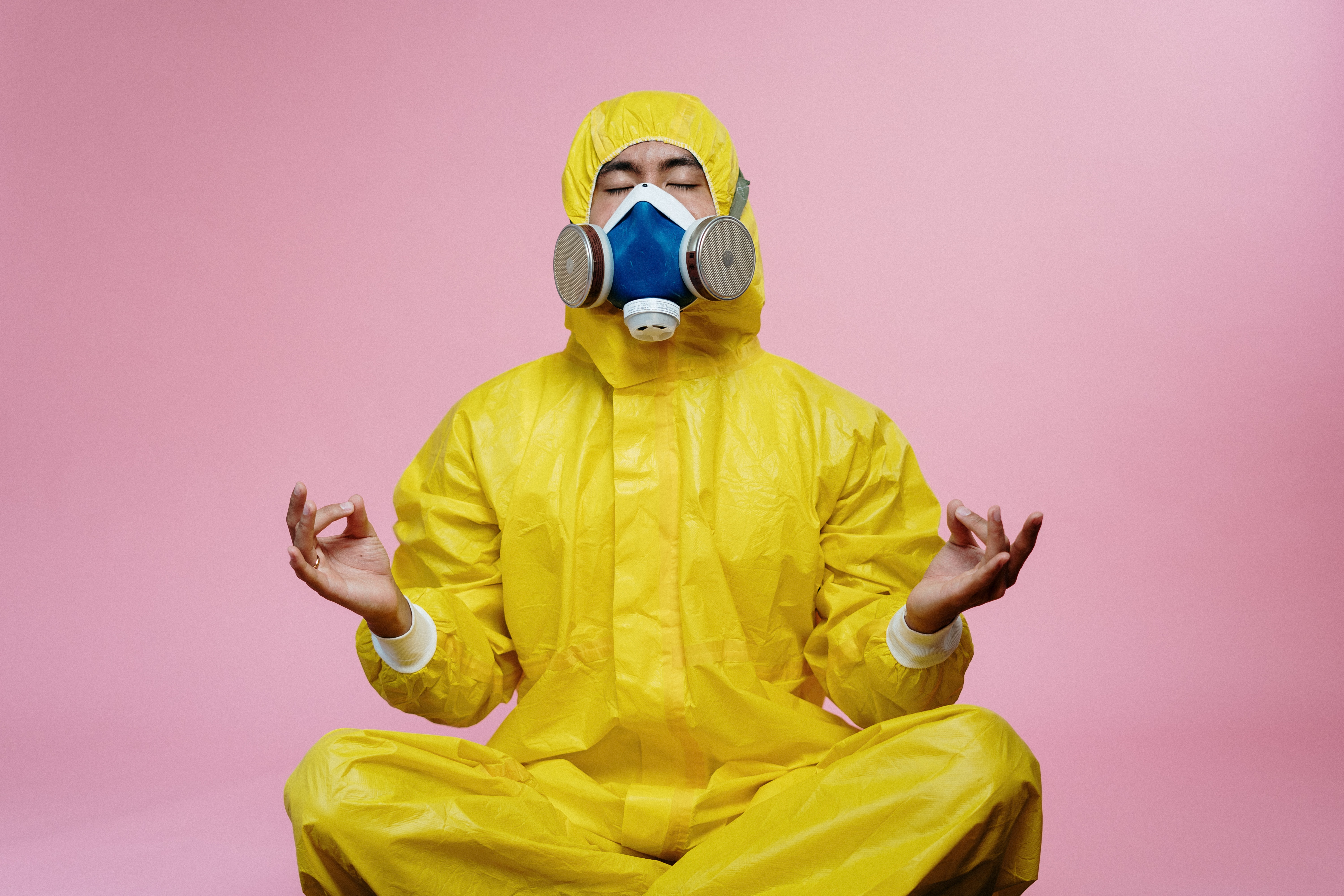 A person dressed in a bright yellow hazmat suit and respirator