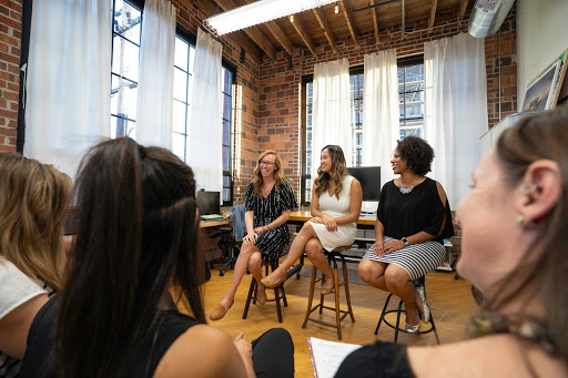 A panel of three smartly dressed yet relaxed women face an audience, over whose shoulders we observe them. The room is chicly decordated, with attractive old-world brick walls, large, industrial-looking windows, and light white curtains only partially obscuring them.