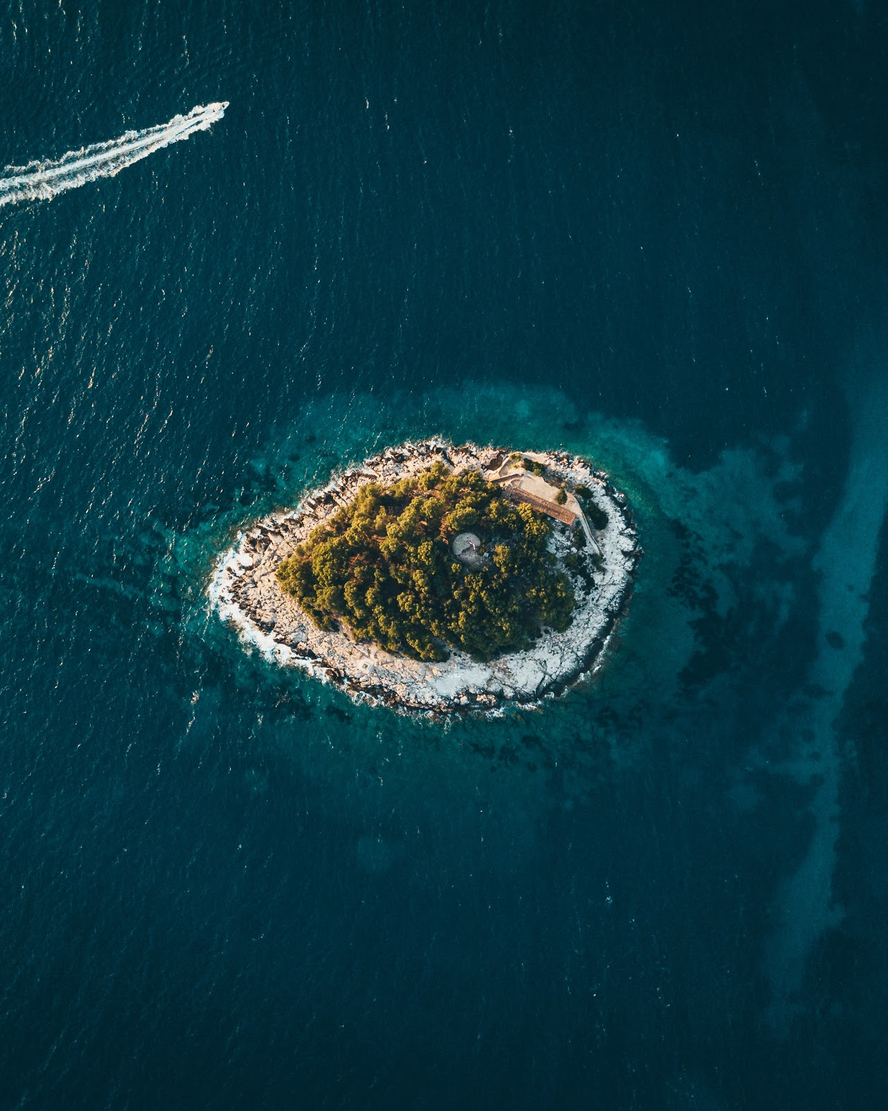 A beautiful island rich with foliage and surrounded by a white shingle sits in the midst of a sparkling azure sea. Toward the top of the frame, a speedboat is passing.