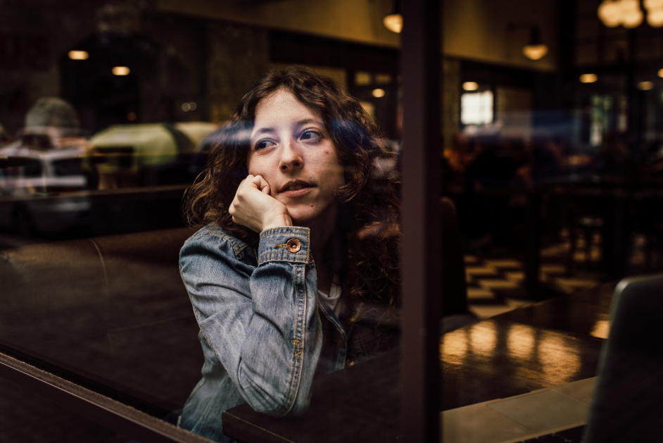 A woman in a denim jacket stares longingly out of a window.