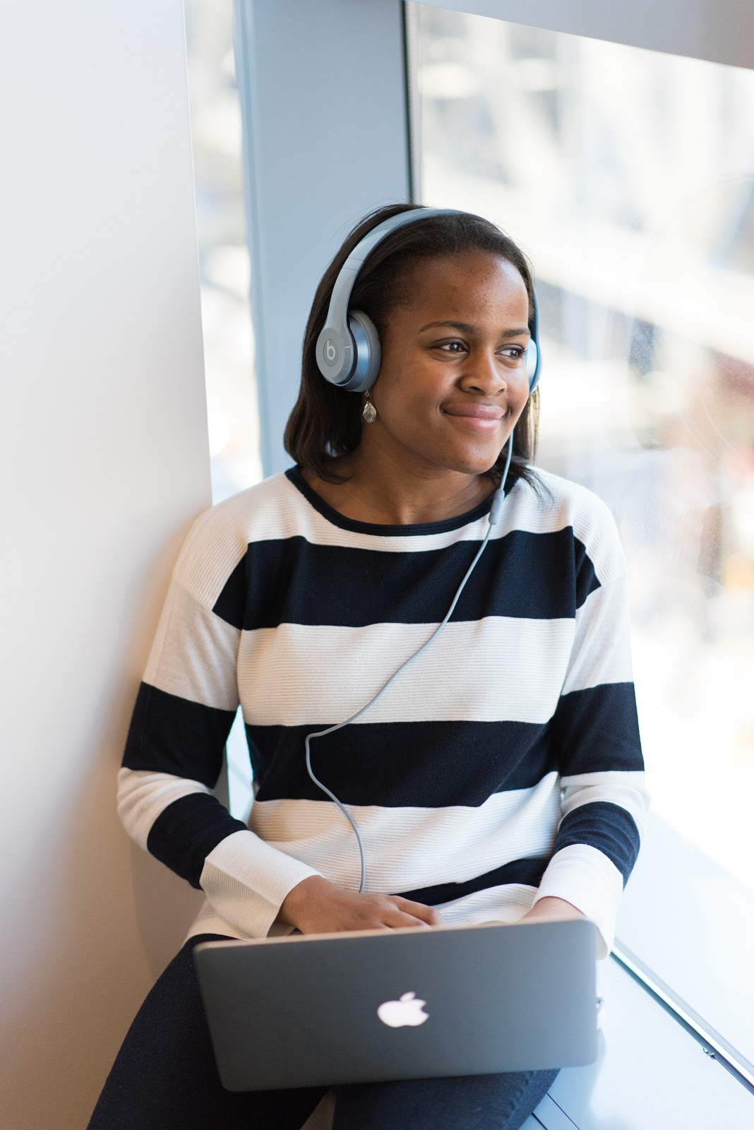 A young woman wearing large headphones listens to music on her laptop while happily gazing out of the window.