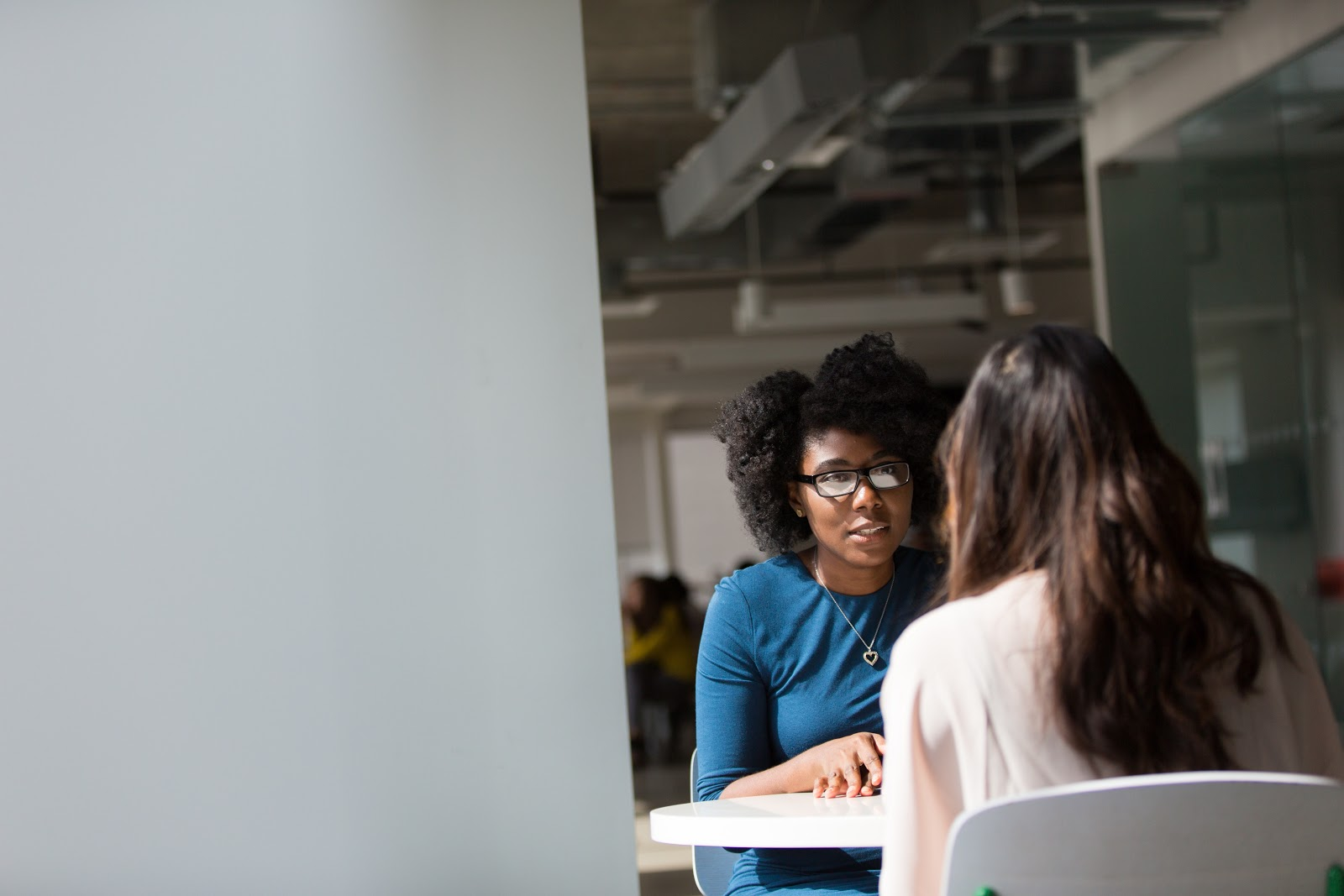 Two women sit in an interview like scenario at a table. One has her back toward us.