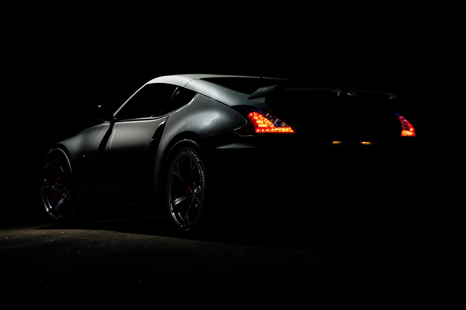 An image of a car in a very dark space. The make or model is hard to determine, but it appears to be sporty and sleek.