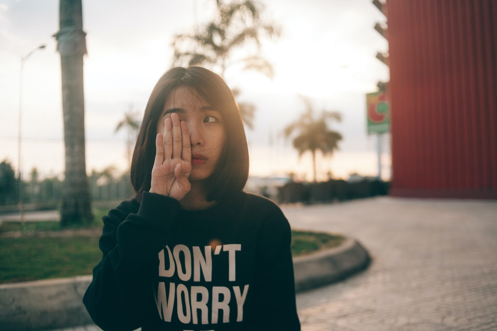 """A young woman wearing a black sweatshirt with words on it reading, """"Don't worry"""" in bold white capital letters."""