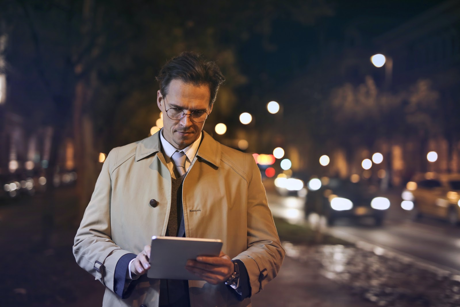A smartly dressed man uses a tablet computer while walking down a city street at night.
