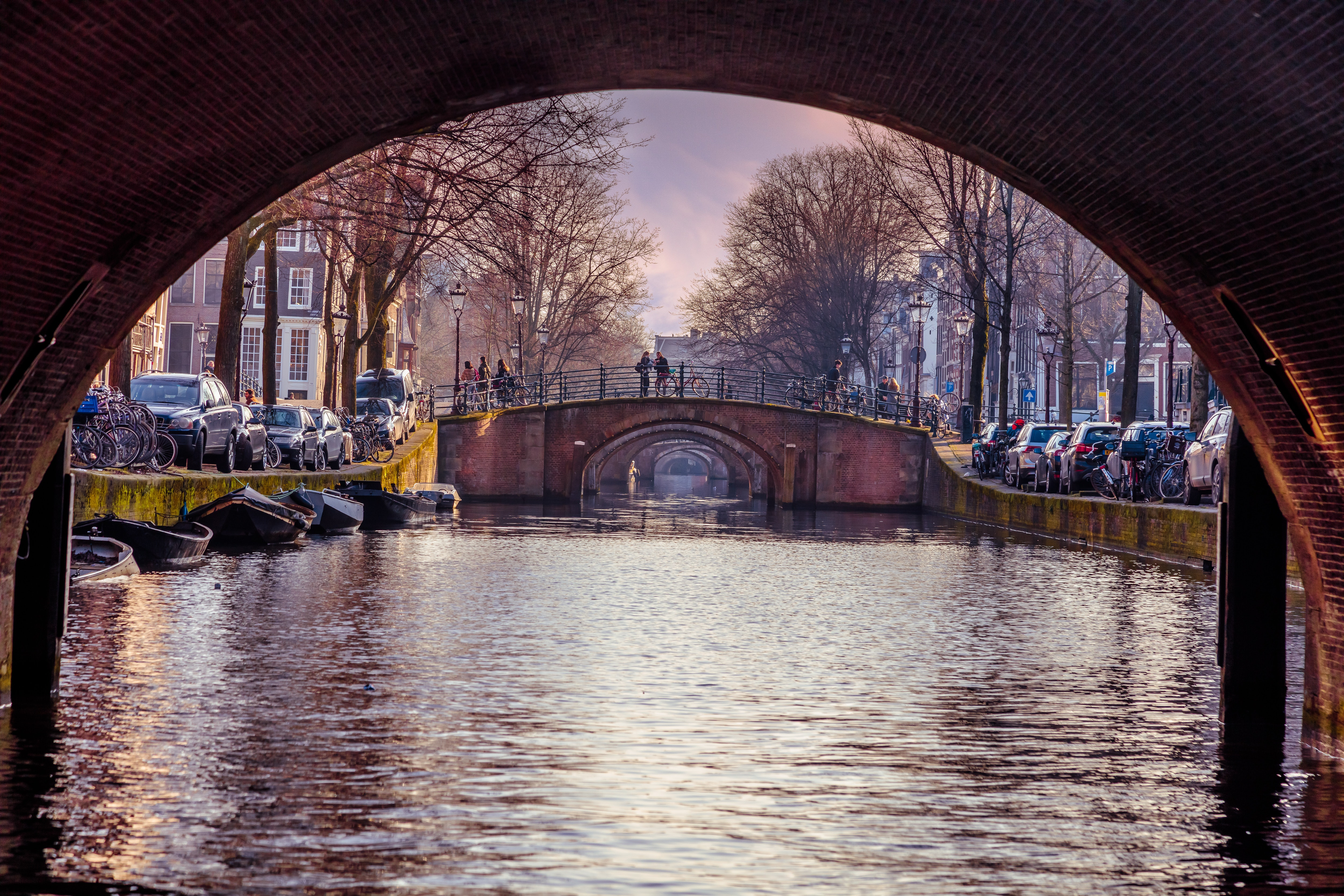 A picture of a canal taken beneath a bridge in Amsterdam.