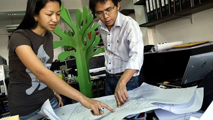 Design your career like an architect designs blueprints devex two employees at the park store office an architect bureau in bangkok discuss a blueprint the blueprint stage of career design involves creating malvernweather Images