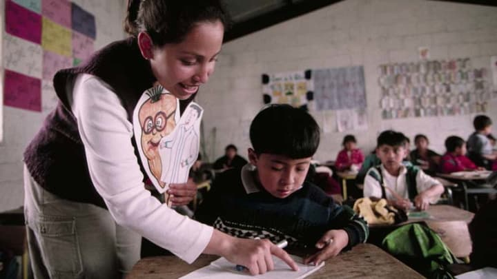 A Peace Corps Volunteer Helps Her Student With His Class Assignment In  Guatemala. Photo By: Peace Corps