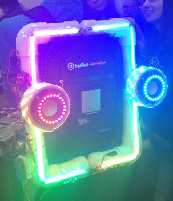 A rectangle of lights surrounds a backpack. There are two circles on the side that are speakers.