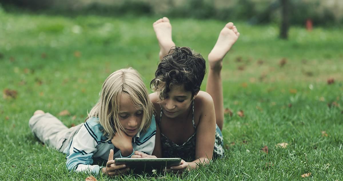 Kinder mit Tablet auf Wiese