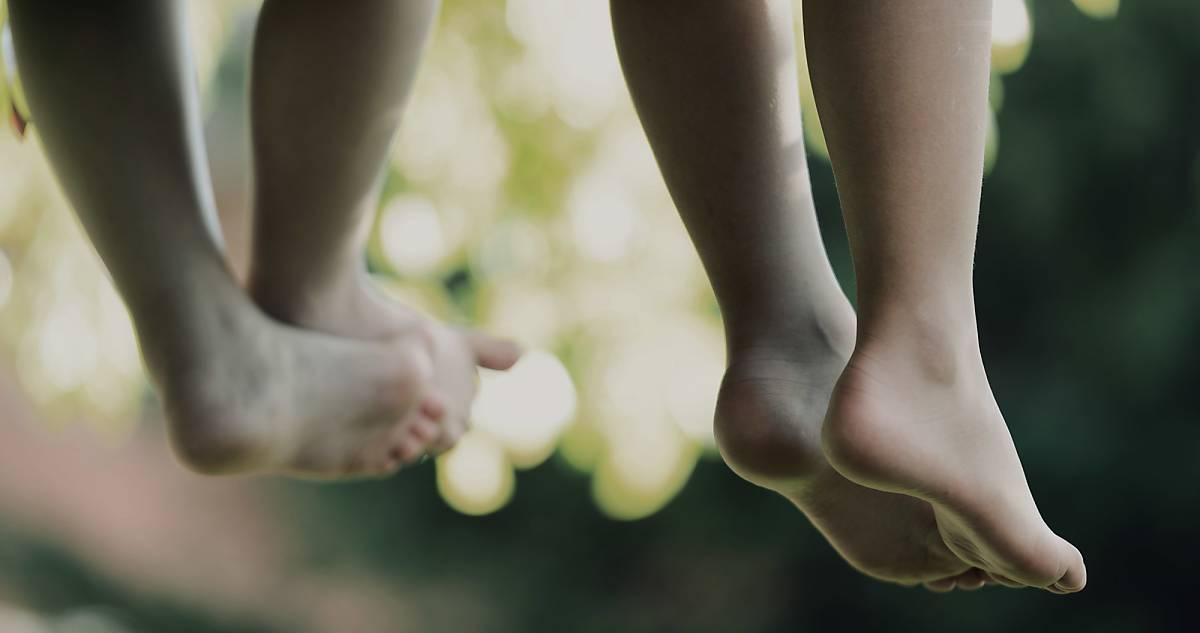 Kinder lassen Beine baumeln