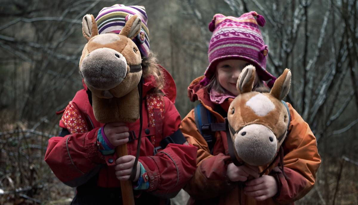Kinder spielen mit Steckenpferden