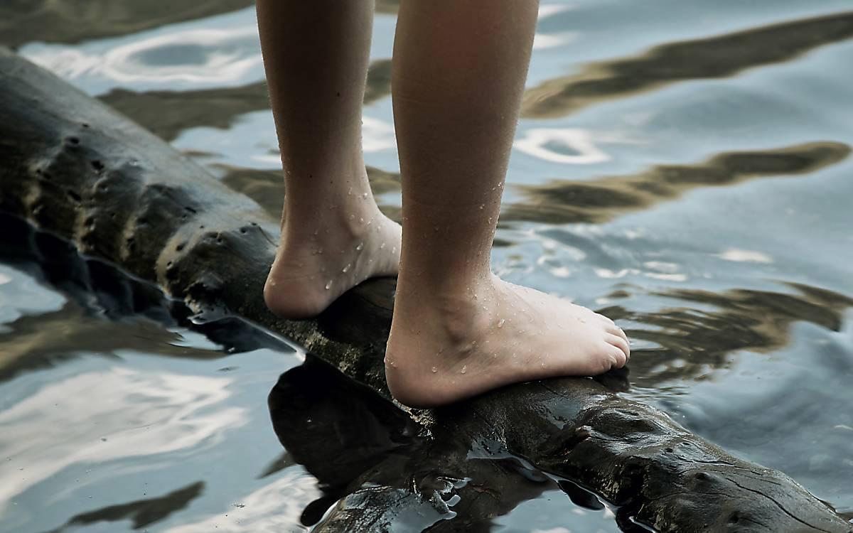 Füße auf einem Stamm im Fluss