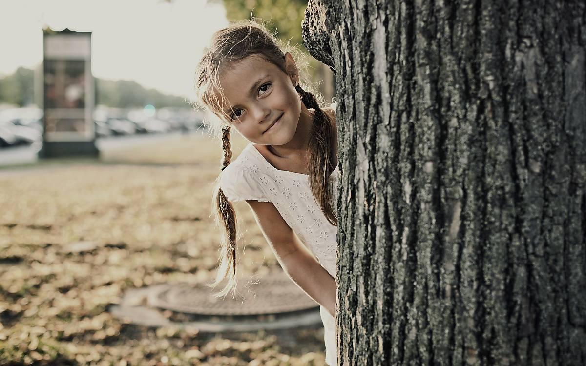 Kind schaut hinter Baum hervor