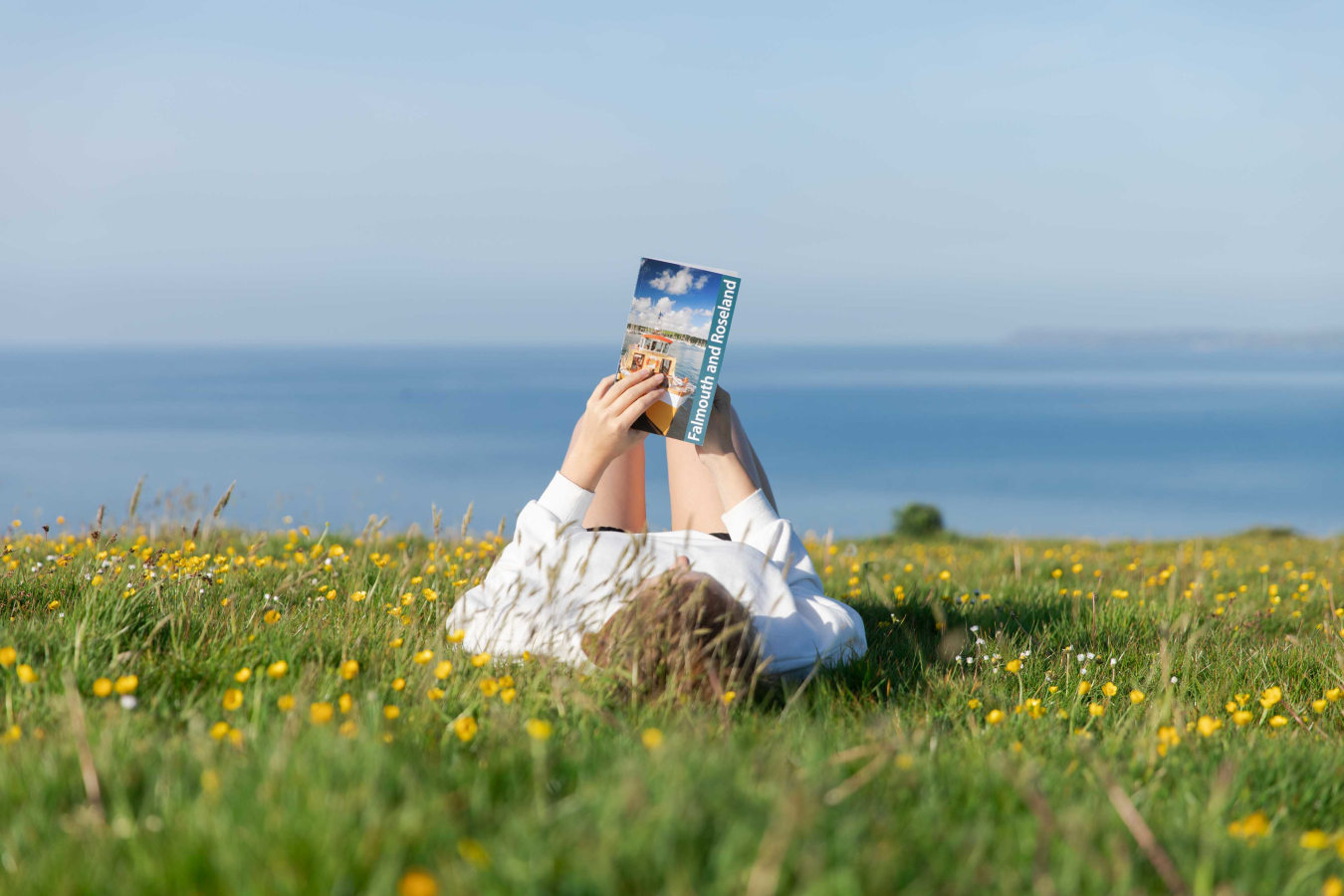 Woman laying on back in grass reading Friendly Guide Book