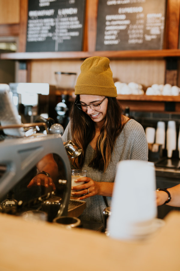 Young woman smiling making coffee in cafe