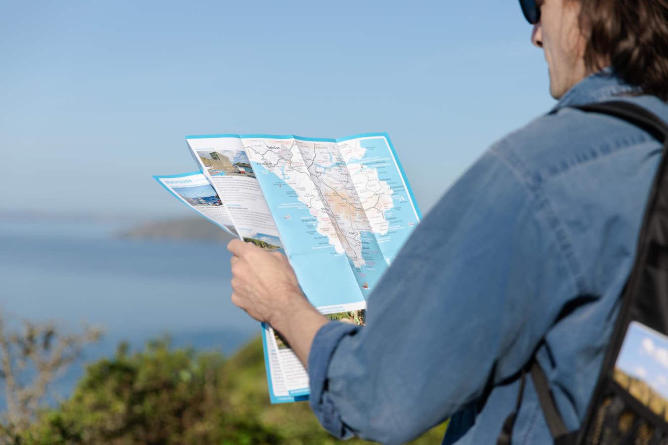 Person holding Friendly Guides Map on Cornish Coast