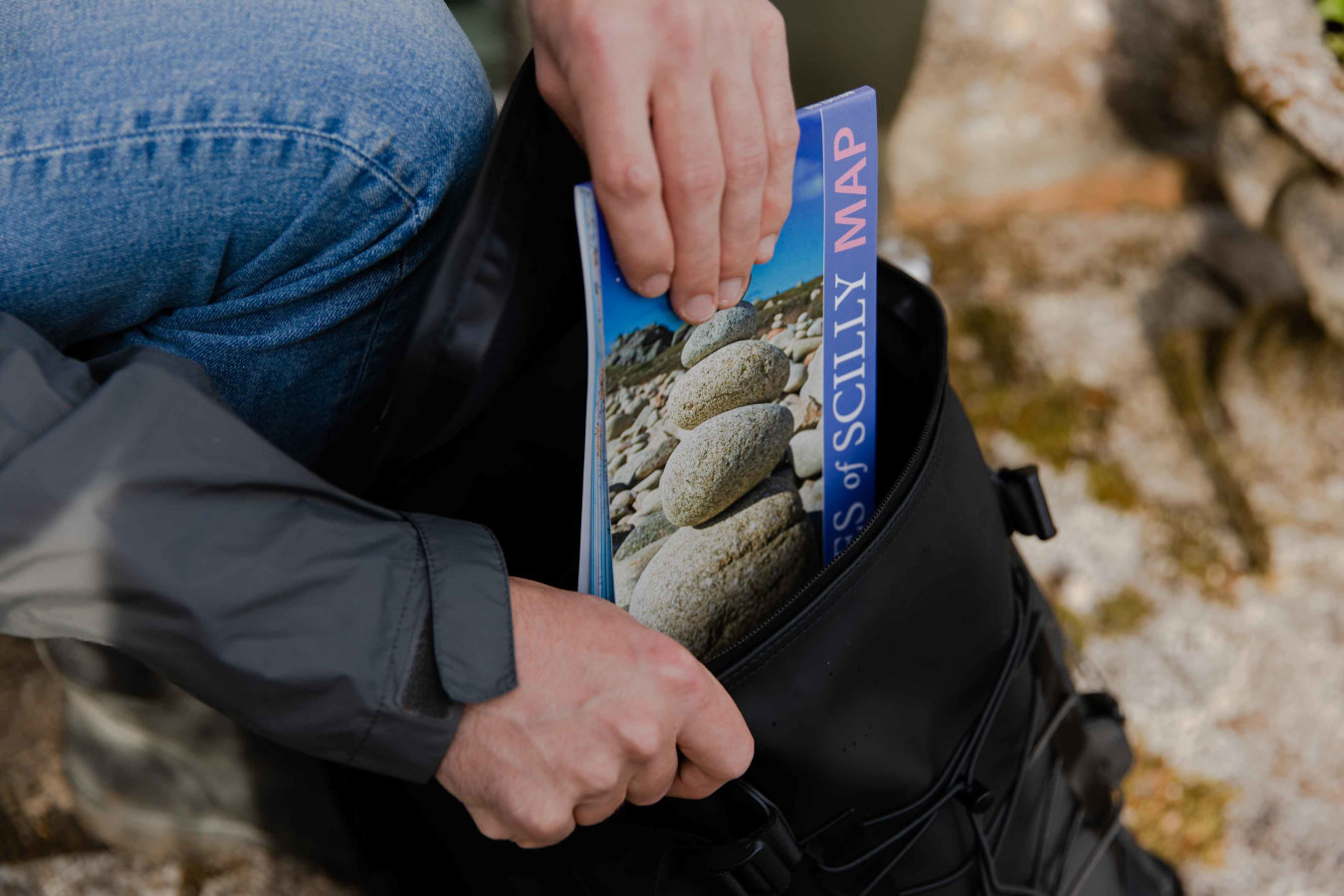 Hands putting Friendly Guides Book into backpack