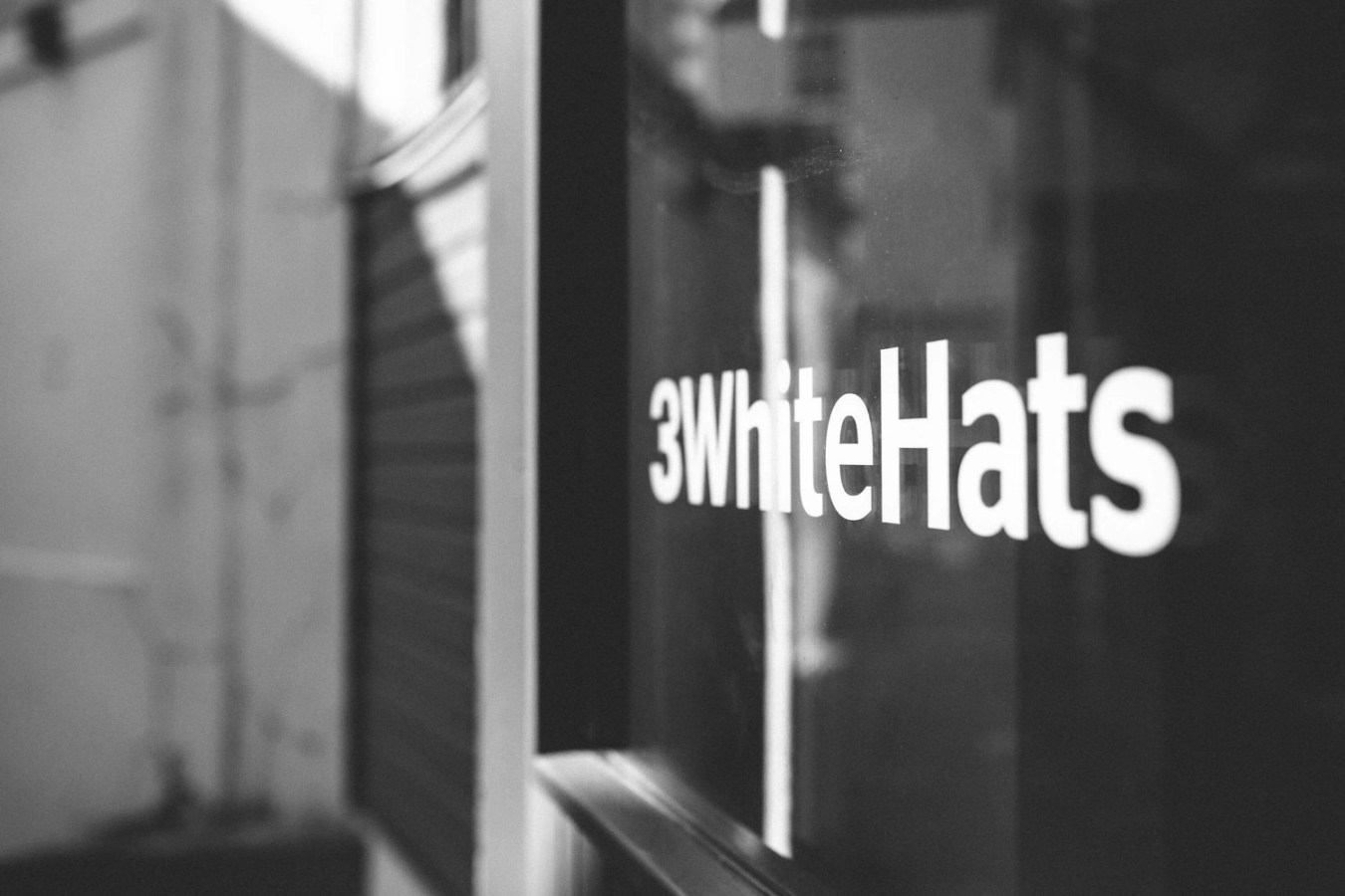 3 white hats building with logo on the window