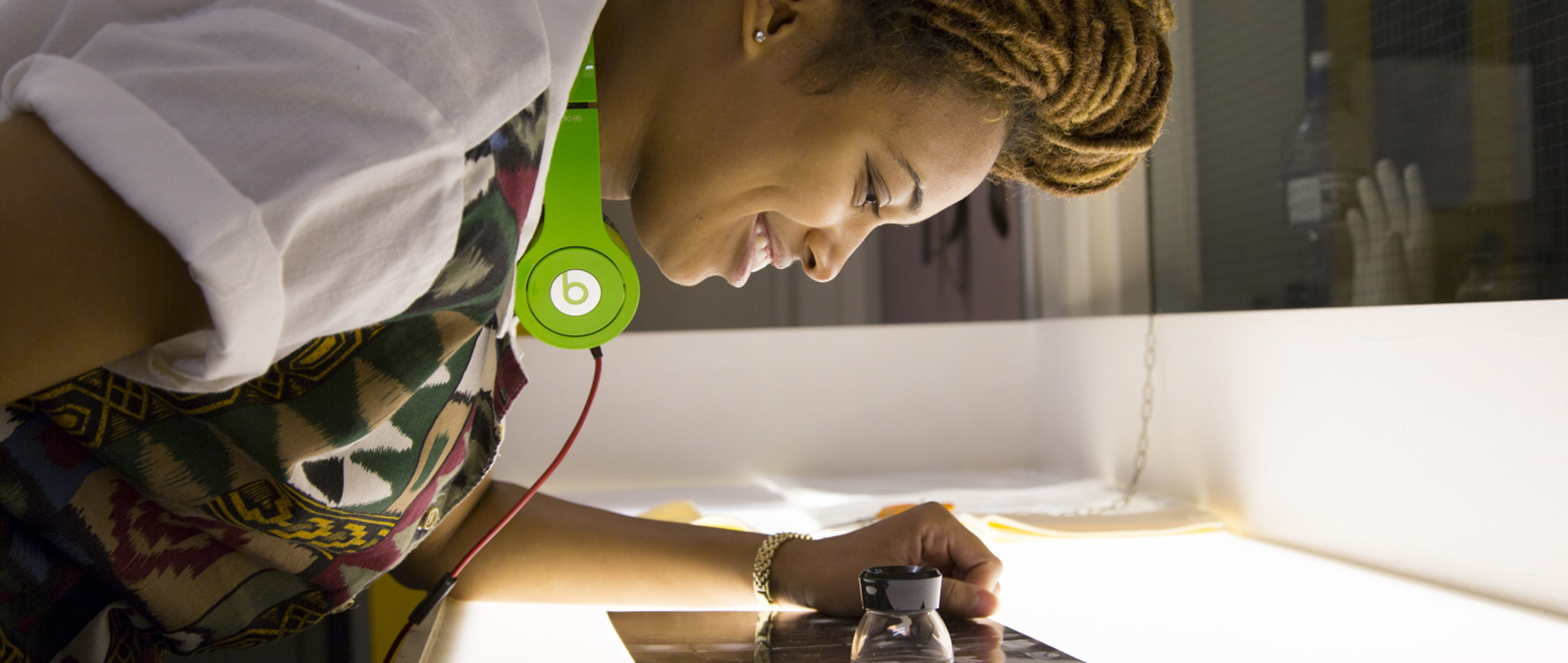 Richmond University image of a young woman wearing beats headphones studying photography