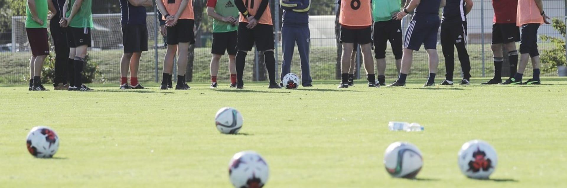 Eine Teilnehmergruppe des Workshops zur DFB-Elite-Jugend-Fortbidung steht auf einem Fußballplatz.