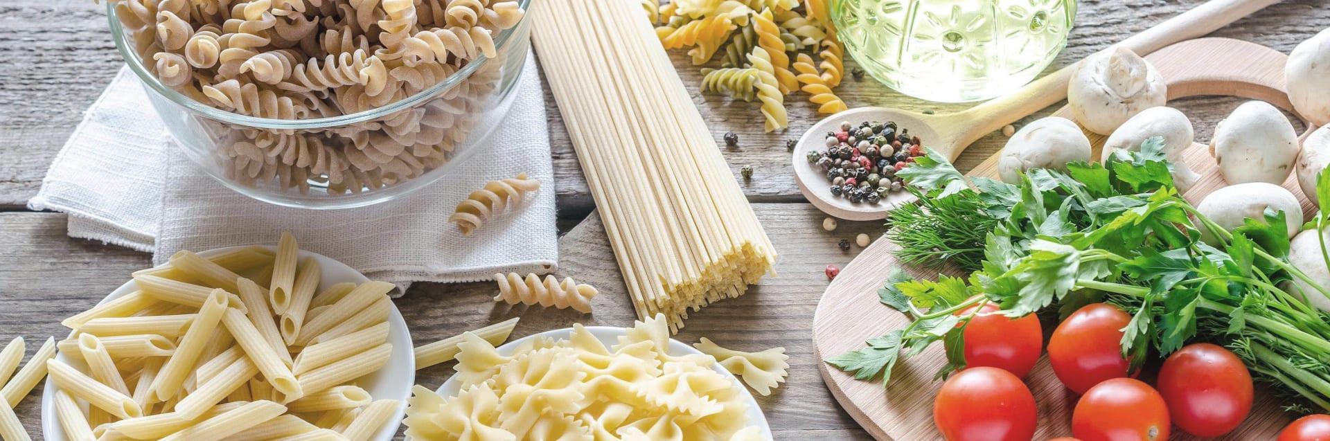 Verschiedene Nudelsorten mit Pilzen, Tomaten, Basilikum und Öl.