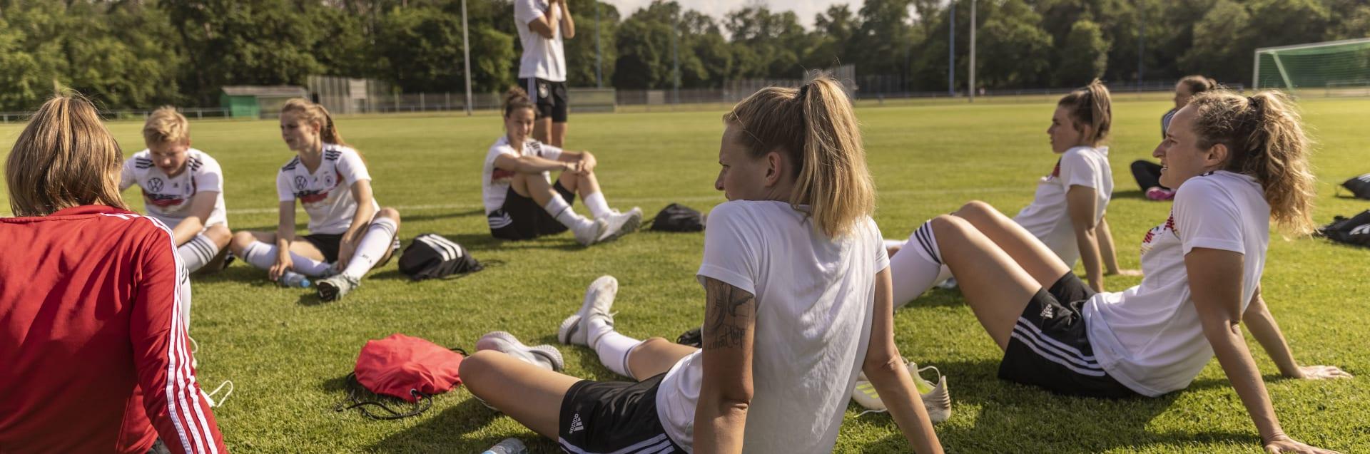 Die Spielerinnen der Frauen Nationalmannschaft sitzen nach einer Trainingseinheit entspannt auf dem Rasen.