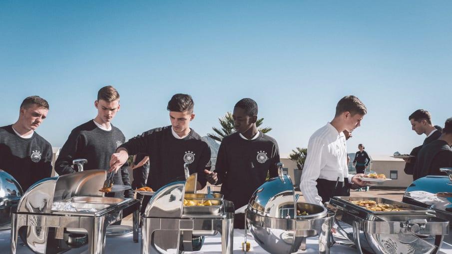 Spieler einer deutschen U-Mannschaft bedienen sich an einem Buffet.