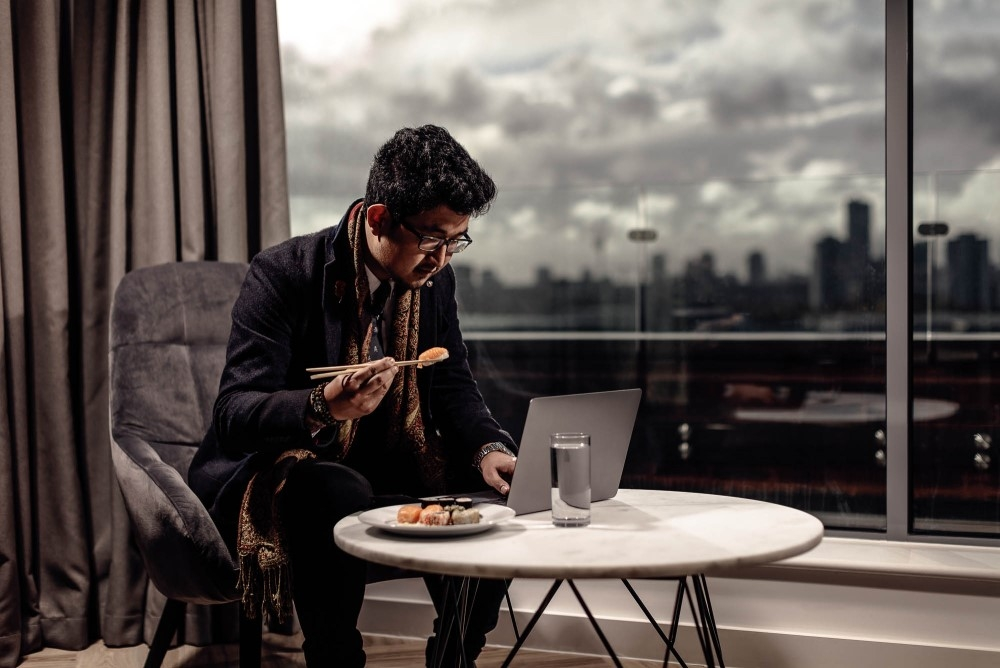 A business traveller working and eating dinner in his Roomzzz apartment.