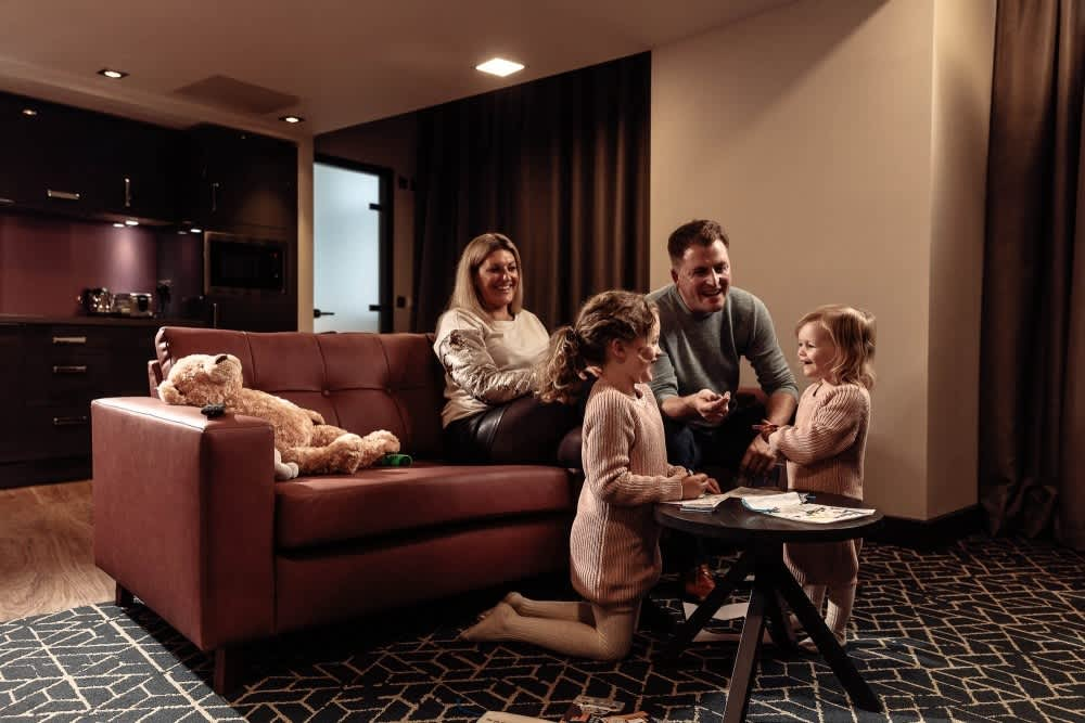 A family sat in the living area of a Roomzzz serviced apartment.