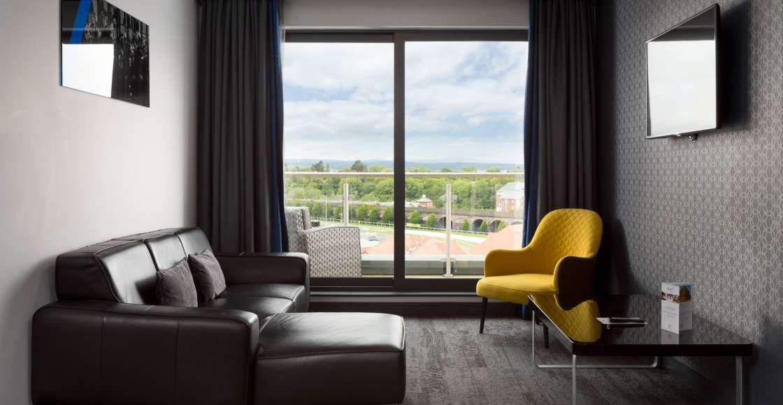 Penthouse suite with sofa, balcony and racecourse view – Serviced Apartment Chester